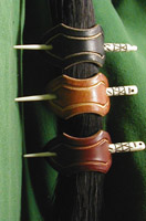 Leather hair barrettes shown in black, dark tan and chestnut leathers.