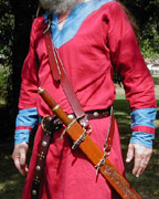 Our Versatile Baldric in Chestnut Leather shown from the side with sword hanging at an angle.