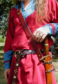 Our Versatile Baldric in Chestnut Leather shown from the side with sword hanging vertically.