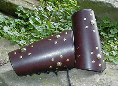 High Chivalry Bracers shown in very dark brown leather. Studs are brass double cap rivets with a nickel mount, pierced by a brass stud, at the center of the pattern. Hand creased edges provide a handsome trim.
