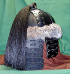 Our leather Mongol Helm shown in black with nickel rivets, natural rabbit fur trim and a horsetail plume of black horse hair.