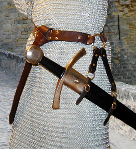 Our Sword Belt of the Circle is based on an example in a late Medieval painting. Shown in dark brown leather with brass hardware.